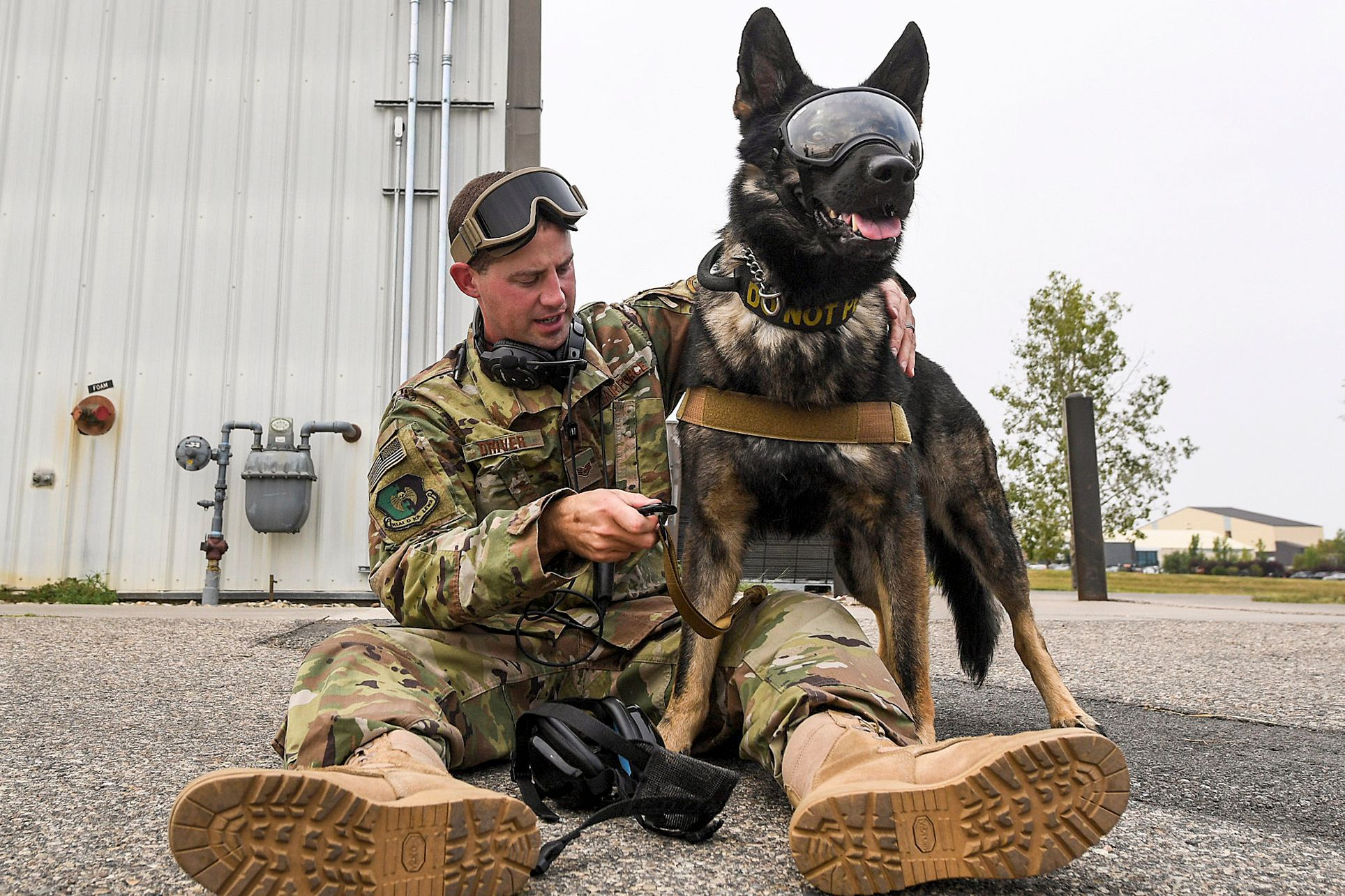 A soldier with a military dog wearing an AR goggle