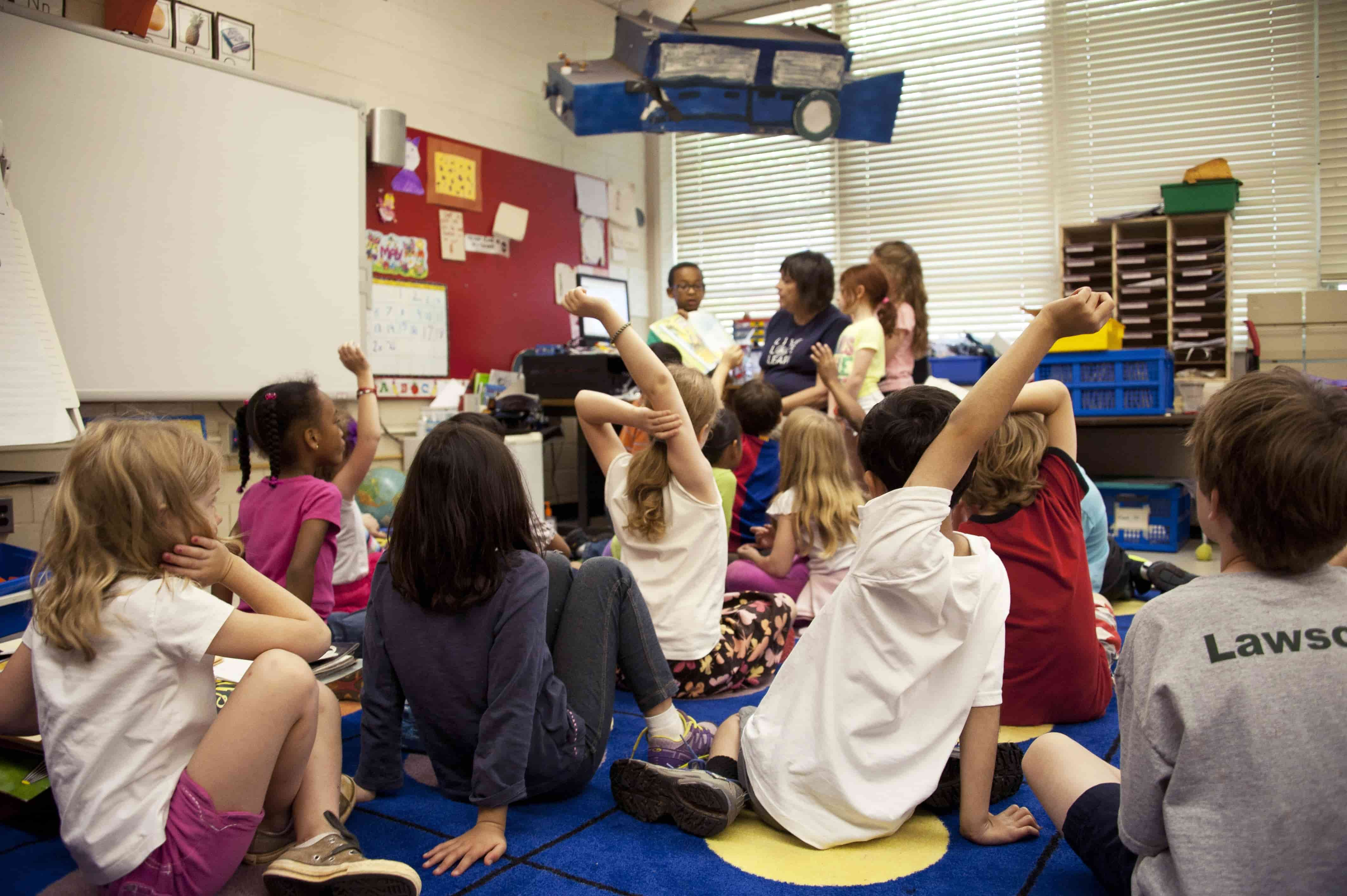 A teacher with her students in a classroom, interacting between each other