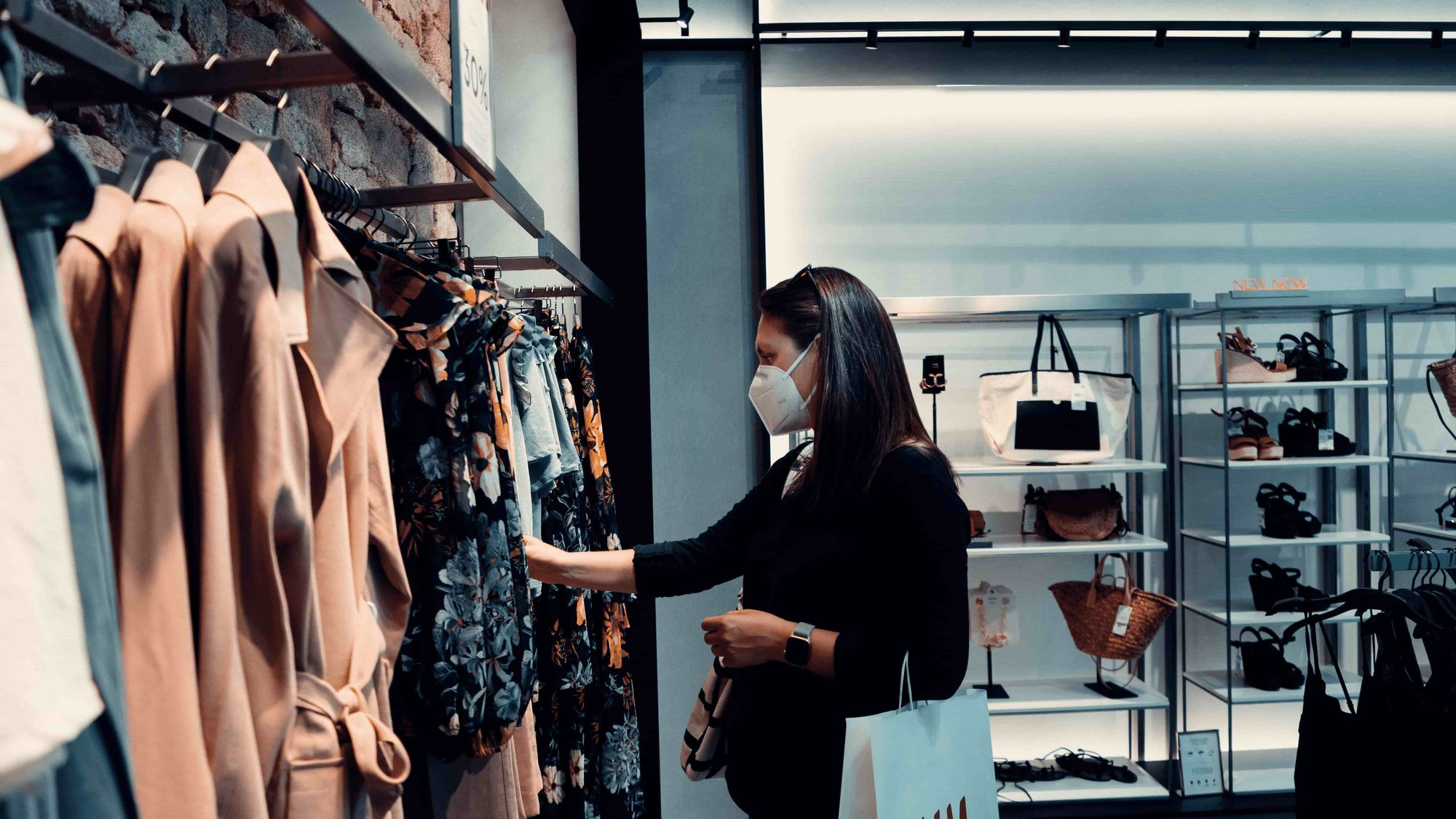 A woman in a store looking at and holding clothes