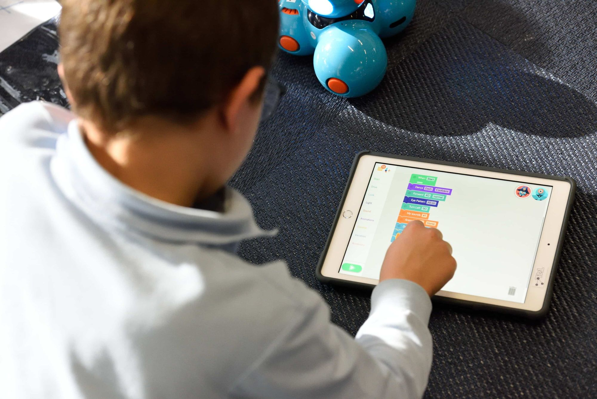 A boy student learning using games on a tablet.