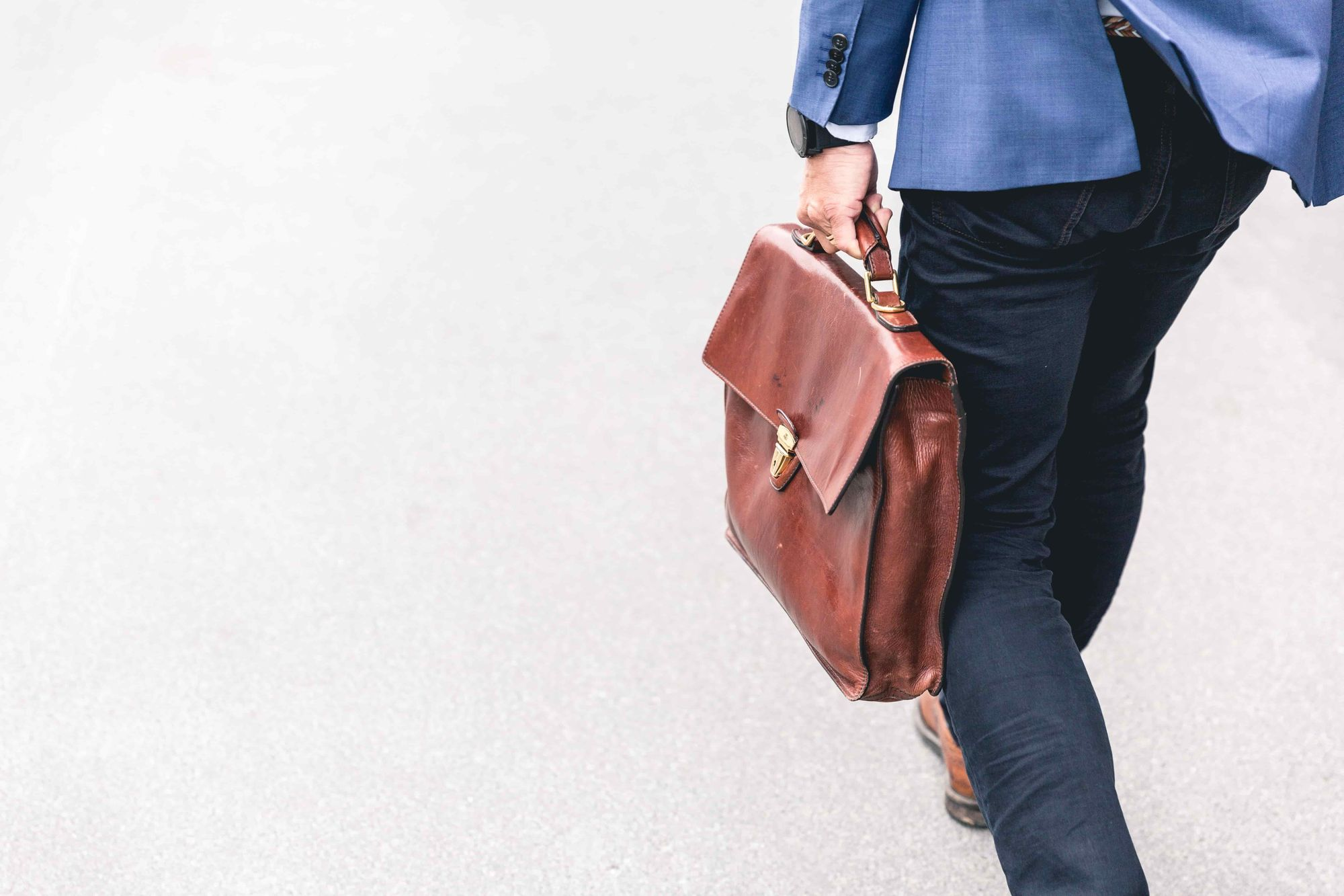 A man walking with a brown suitcase into work.