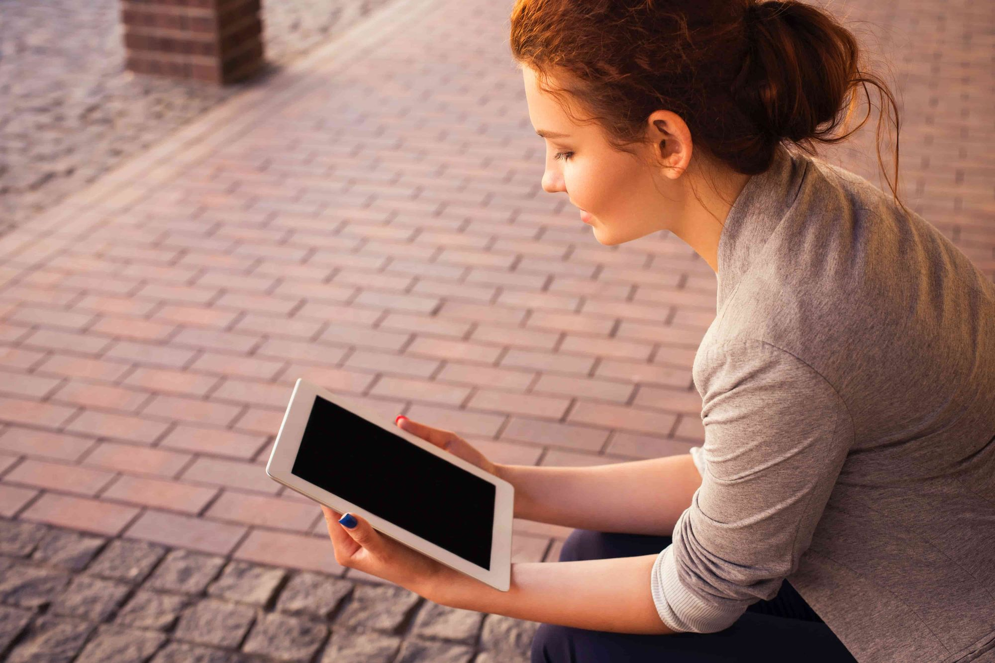 A woman sitting while reading on her iPad.