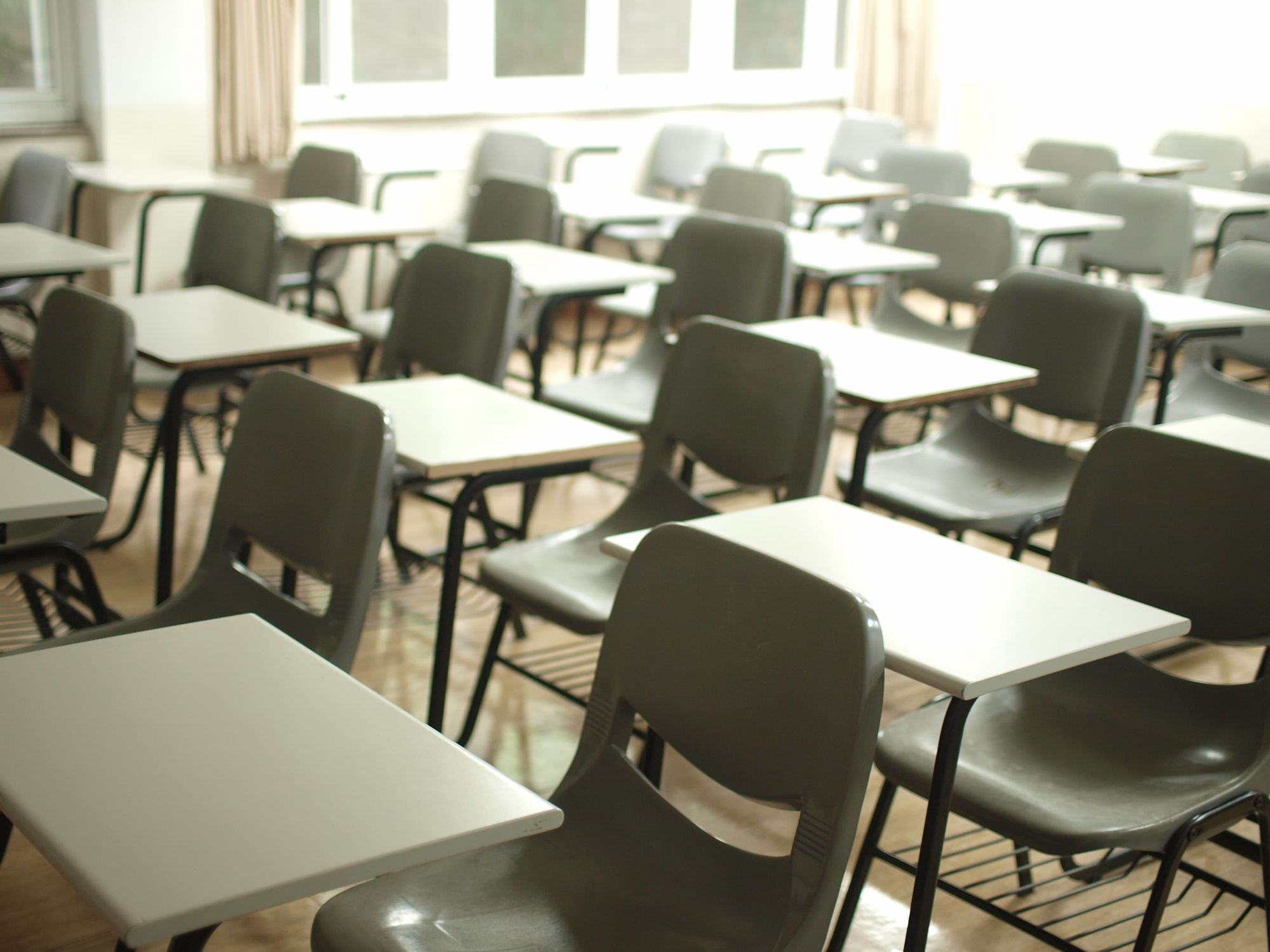 Empty tables and seats in a classroom.