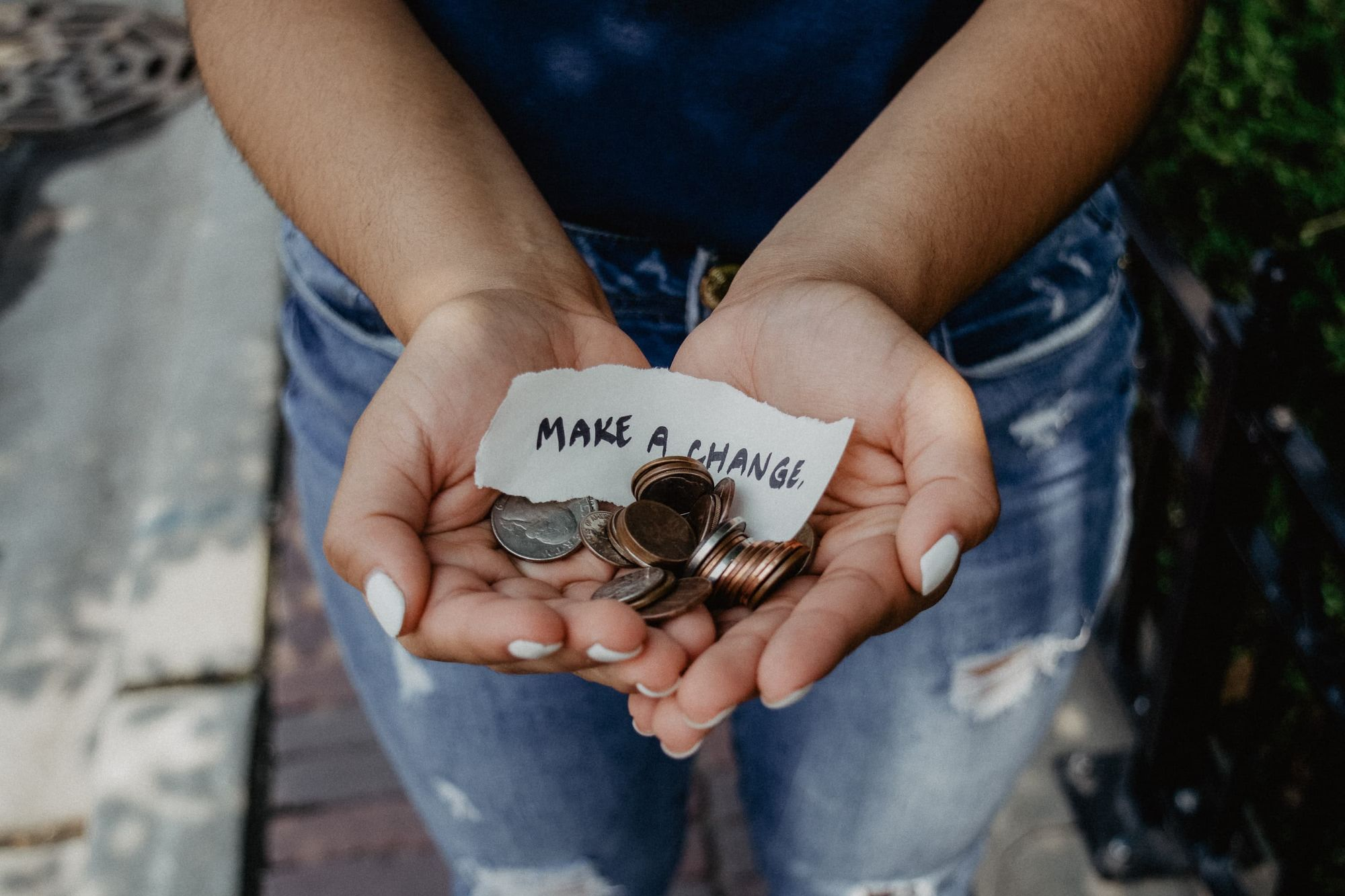 """Two hands holding coins and a writing that says, """"Make a change""""."""