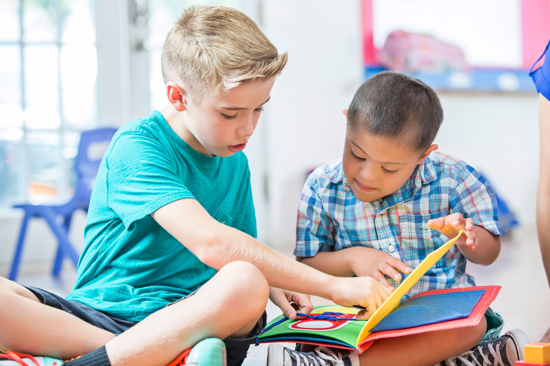 A boy helping his friend with disability to read a book.