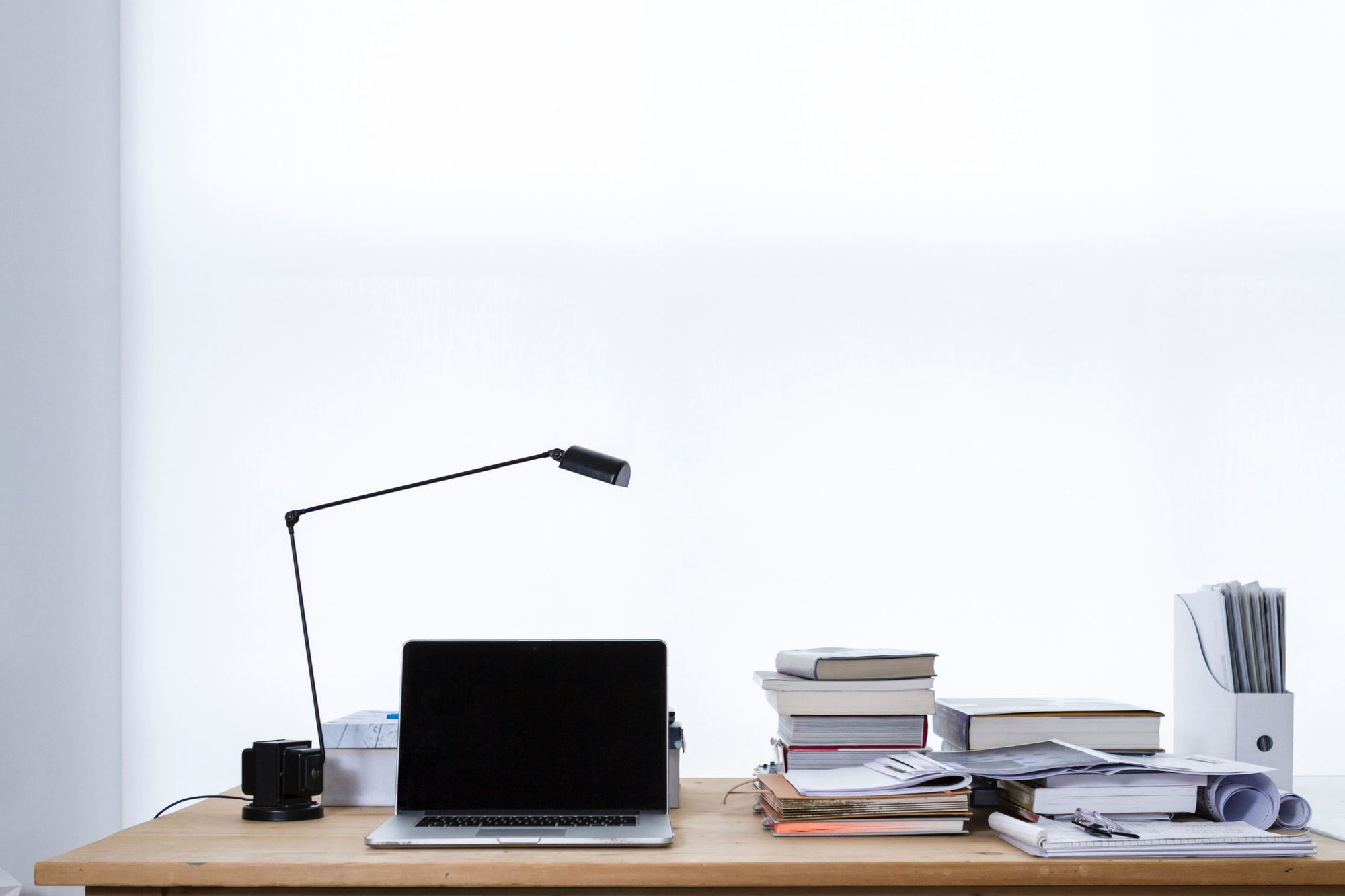 A learning desk consists of a laptop and books.