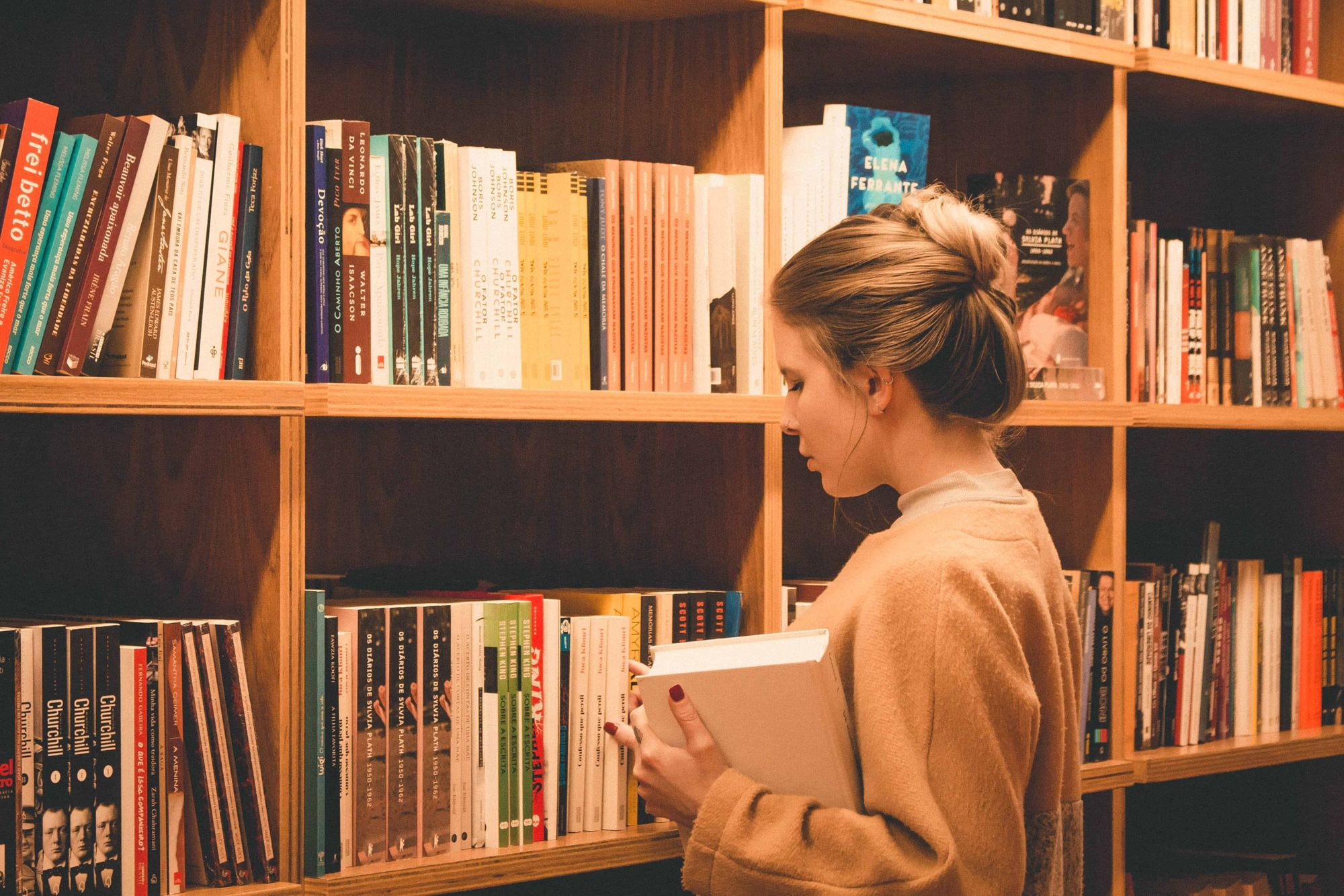 A woman choosing a book in a library.