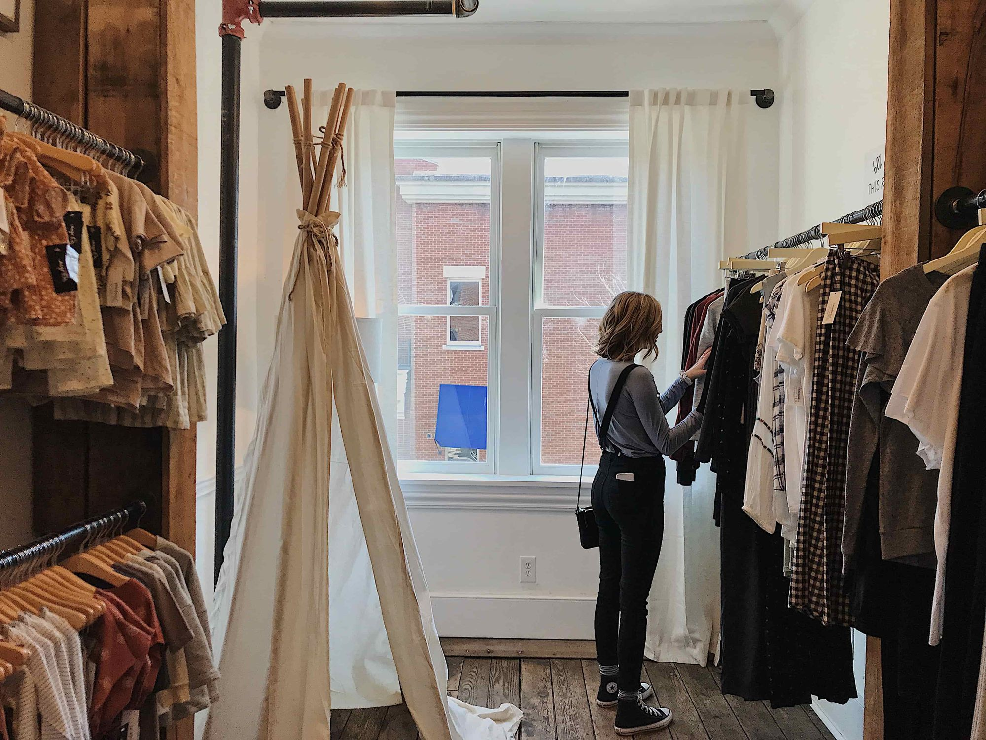 A woman looking at a cloth on a cloth store.