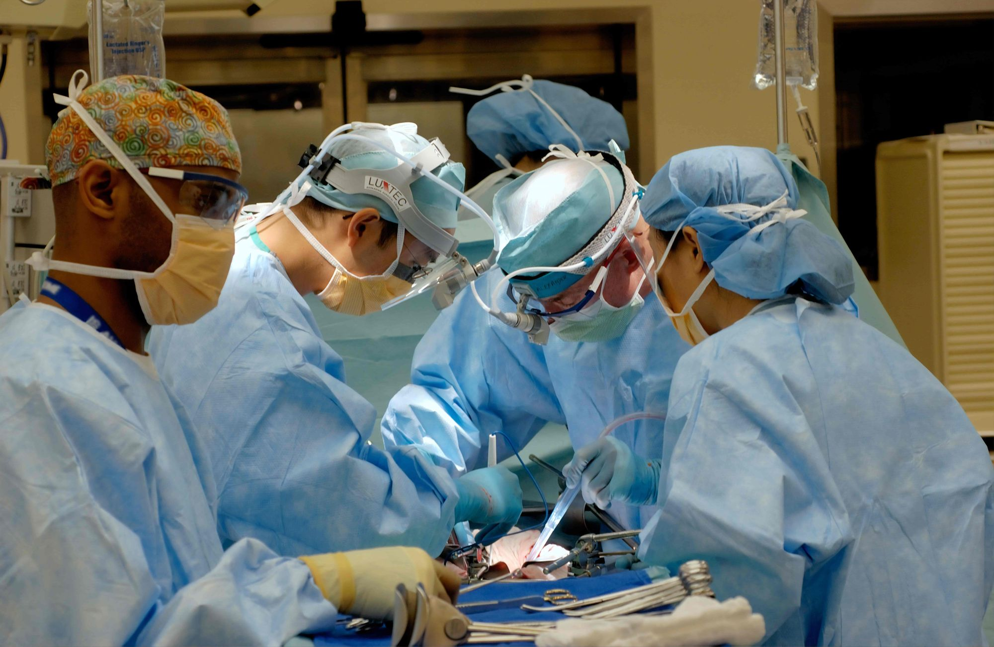 A few surgeons are operating on a patient.